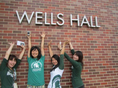 four girls in spartan apparel with their arms up in front of a red brick building named 'Wells Hall'
