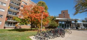 picture of a red brick dormitory with autumn colored trees and bikes at a bike rack