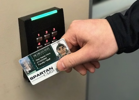 picture of someone holding their MSU ID against a card reader