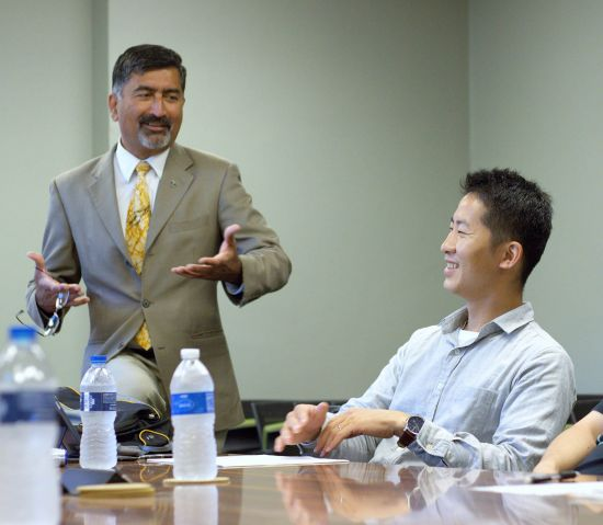 picture of a man in a suit presenting, a man is seen sitting to his right and smiling