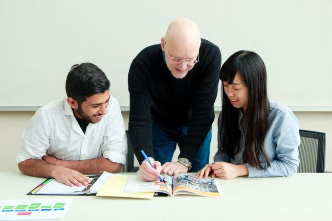 picture of a bald professor in black turtleneck teaching two students who are sitting at a table to the left and right of him