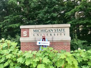 Student in front of MSU Sign holding Fulbright Sign