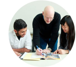 An English instructor works with two smiling international students